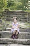 Chica joven en los pasos de la roca que parecen agujereados Imagen de archivo libre de regalías