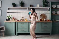 Chica joven en los pijamas que bailan por mañana en la cocina imagen de archivo libre de regalías