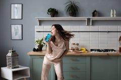Chica joven en los pijamas que bailan por ma?ana en la cocina imágenes de archivo libres de regalías