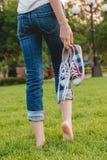 Chica joven en los vaqueros que sostienen las zapatillas de deporte en su mano Foto de archivo