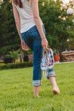 Chica joven en los vaqueros que sostienen las zapatillas de deporte en su mano Foto de archivo libre de regalías