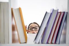 Chica joven en los vidrios que alcanzan para un libro imagen de archivo libre de regalías