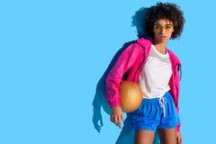 Chica joven en los vidrios que sostienen la bola del baloncesto y que miran lejos en fondo azul foto de archivo libre de regalías