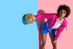 Chica joven en los vidrios que sostienen la bola del baloncesto y que miran lejos en rosa y azul fotos de archivo