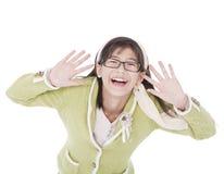Chica joven en manos verdes del suéter y de los vidrios alrededor de la cara, smili Imágenes de archivo libres de regalías