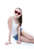 Chica joven en pantalones cortos y una camiseta en un fondo blanco Fotos de archivo libres de regalías