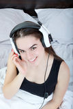 Chica joven en pijamas con reproductor Mp3 o móvil y auriculares Imagen de archivo