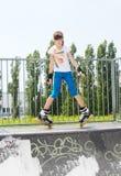 Chica joven en rollerblades en una rampa Foto de archivo