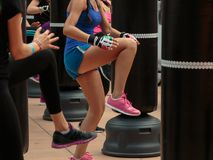 Chica joven en ropa de deportes azul: Entrenamiento de la aptitud y del boxeo con el saco de arena Imagen de archivo libre de regalías