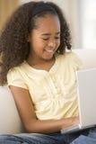 Chica joven en sala de estar usando la computadora portátil y la sonrisa Imagenes de archivo