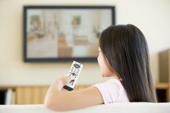 Chica joven en sitio con la televisión de la pantalla plana Foto de archivo libre de regalías