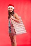 Chica joven en sombrero del `s de Santa con el bolso de compras Foto de archivo