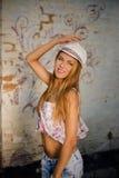 Chica joven en sombrero del sombrero de ala que sonríe al lado de la pared con Imágenes de archivo libres de regalías