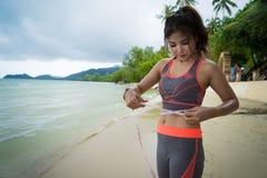 Chica joven en sportwear con la cinta métrica en la playa del mar - peso imagen de archivo libre de regalías
