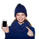 Chica joven en suéter, bufanda y el sombrero del punto que sostiene el teléfono Foto de archivo