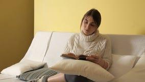 Chica joven en suéter caliente acogedor en el invierno que iguala en casa, libro de lectura almacen de video