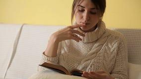 Chica joven en suéter caliente acogedor en el invierno que iguala en casa, libro de lectura metrajes