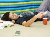 Chica joven en suelo que ve la TV Imagen de archivo libre de regalías