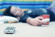 Chica joven en suelo que ve la TV Foto de archivo