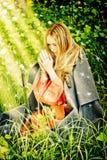 Chica joven en sus rodillas que ruega en maderas Foto de archivo libre de regalías