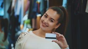 Chica joven en tienda con la tarjeta de las compras y de crédito almacen de video
