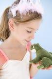 Chica joven en traje de la princesa que besa la rana de la felpa Foto de archivo libre de regalías