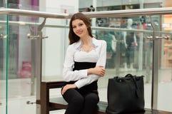 Chica joven en un banco en un centro comercial Fotos de archivo