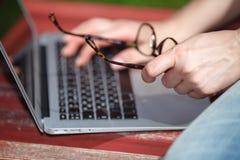 Chica joven en un banco con un ordenador portátil Imagen de archivo libre de regalías