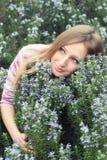 Chica joven hermosa en un campo de hierba del romero Foto de archivo libre de regalías