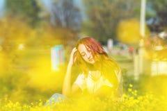 Chica joven en un campo del césped con las flores amarillas Foto de archivo