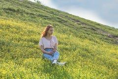 Chica joven en un campo del césped con las flores amarillas Fotografía de archivo libre de regalías