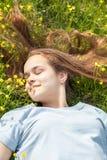 Chica joven en un campo del césped con las flores amarillas Imágenes de archivo libres de regalías