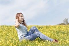 Chica joven en un campo del césped con las flores amarillas Fotos de archivo