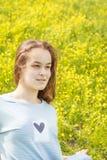 Chica joven en un campo del césped con las flores amarillas Imagen de archivo libre de regalías