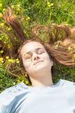 Chica joven en un campo del césped con las flores amarillas Foto de archivo libre de regalías