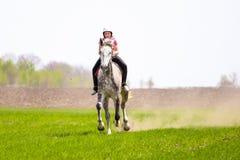 Chica joven en un casco que monta un caballo dapple-gris en un campo de hierba Imágenes de archivo libres de regalías