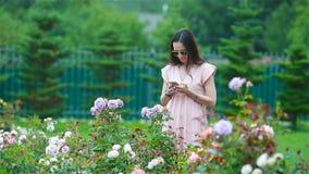 Chica joven en un jardín de flores entre rosas hermosas Olor de rosas almacen de video