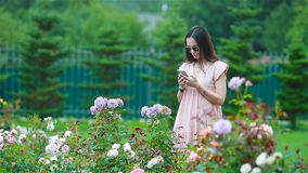 Chica joven en un jardín de flores entre rosas hermosas Olor de rosas almacen de metraje de vídeo
