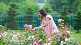 Chica joven en un jard?n de flores entre rosas hermosas Olor de rosas metrajes