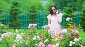 Chica joven en un jard?n de flores entre rosas hermosas Olor de rosas almacen de video