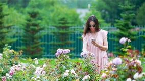 Chica joven en un jard?n de flores entre rosas hermosas Olor de rosas almacen de metraje de vídeo