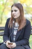 Chica joven en un parque en un banco que escucha la música Foto de archivo