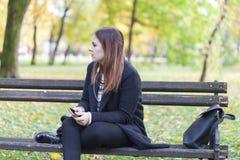 Chica joven en un parque en un banco que escucha la música Imagenes de archivo