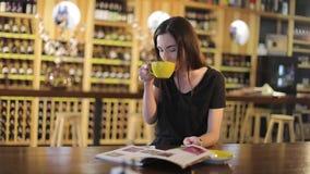 Chica joven en un restaurante con una taza de café caliente, disfrutando del aroma y del sabor del café mientras que se relaja en almacen de metraje de vídeo