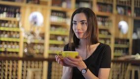 Chica joven en un restaurante con una taza de té, disfrutando del aroma y del sabor del café mientras que se relaja en la cafeter almacen de video