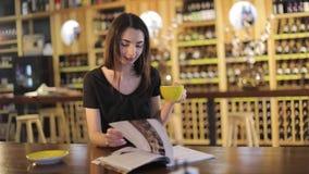 Chica joven en un restaurante con una taza de té, disfrutando del aroma y del sabor del café mientras que se relaja en la cafeter metrajes