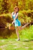 Chica joven en un sombrero de paja en el río Imágenes de archivo libres de regalías