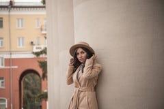 Chica joven en un sombrero y una capa en el fondo de las columnas del teatro Fotografía de archivo libre de regalías