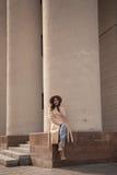 Chica joven en un sombrero y una capa en el fondo de las columnas del teatro Fotos de archivo
