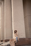 Chica joven en un sombrero y una capa en el fondo de las columnas del teatro Fotos de archivo libres de regalías